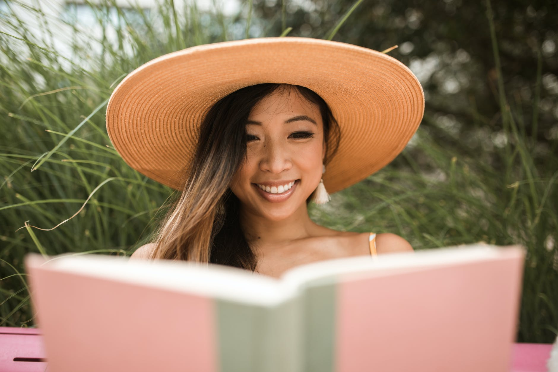 smiling woman wearing a sun hat and reading a book